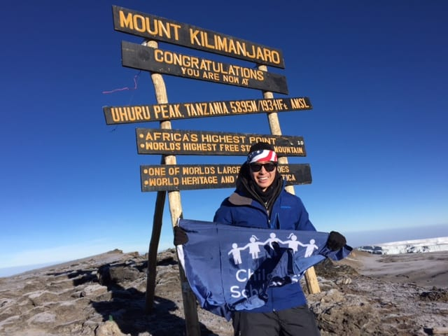 Kevin Song waves his CSF flag at Mt. Kilimanjaro's Uhuru Peak.